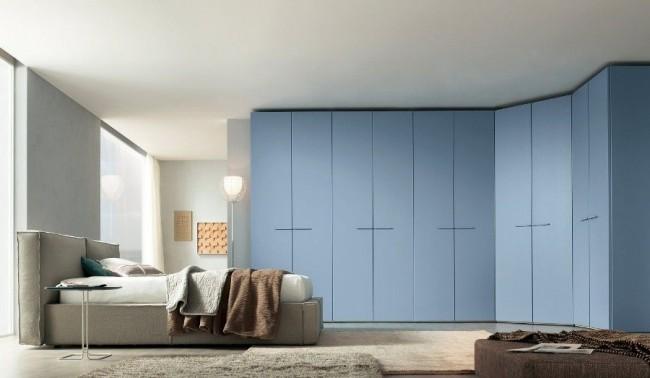 Корпусный угловой шкаф голубого цвета в современной спальне