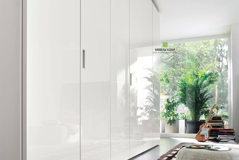 Белый глянцевый шкаф с лакированными дверями и вырезанными ручками