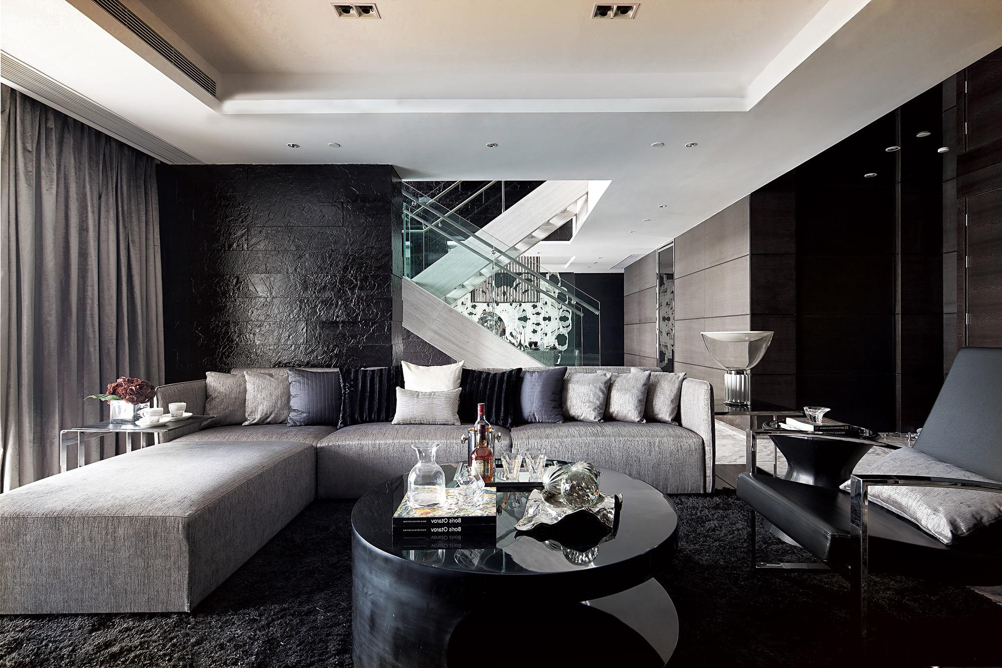 Черная комната с большим серым диваном