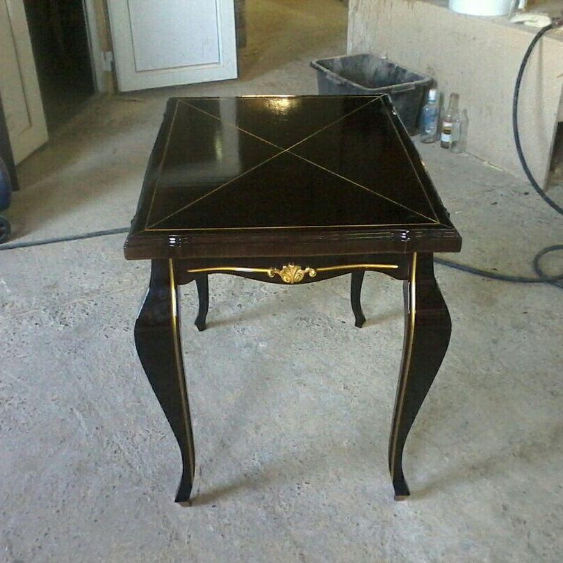 Стол черного цвета с элемента золотого цвета