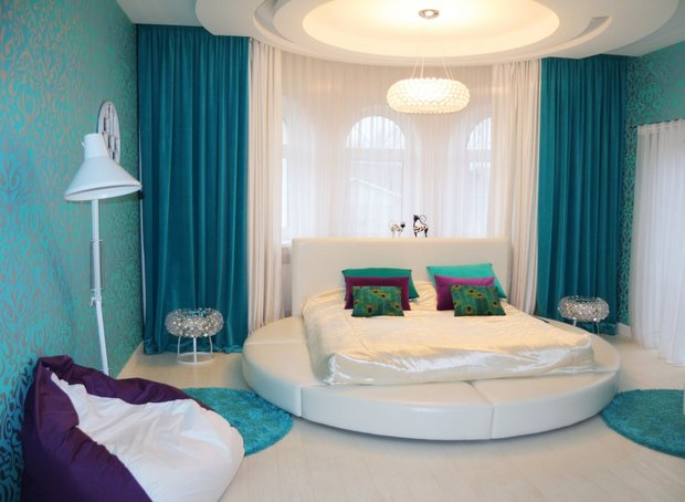Бирюзрвые оттенки комнаты с красивой кроватью
