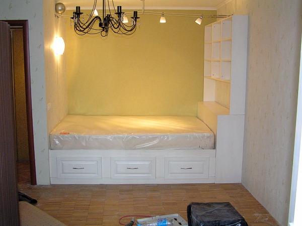 Кровать встроенная в нишу в окружении шкафчиков