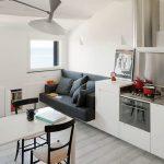 Черный диван в интерьере белой кухни
